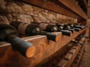 closeup-shot-of-dusty-wine-bottles-on-a-wooden-wine-rack-old-wine-cellar-with-wine-bottles_t20_oRYLPP
